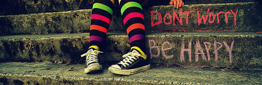 "A woman with colorful striped socks sitting on steps with ""Don't worry be happy"" written in colorful chalk on the steps."