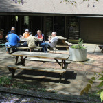 People sitting outside at picnic table with a shared meal