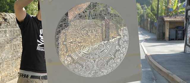 Papercut of the Mayan calendar projected on sidewalk