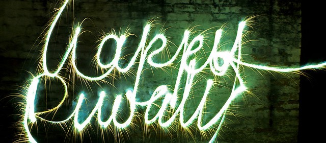 Happy Diwali written in burning rope against a brick background