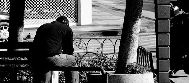 Man sitting alone on a bench with his back to the camera, black and white photo